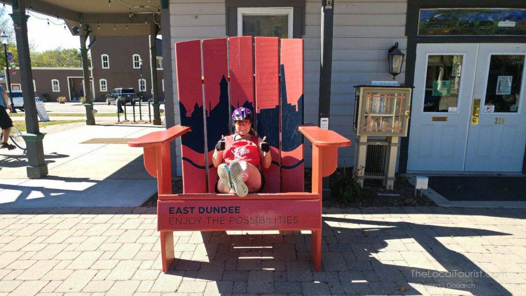 Theresa taking a break from riding her bike and sitting in a giant chair.