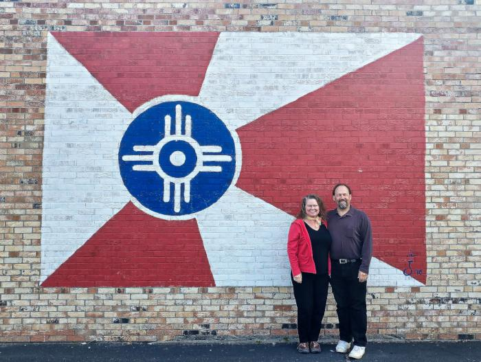 Jim and Theresa in front of the Doo-Dah Diner mural of the Kansas flag
