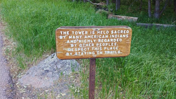Sign informing visitors to respect the sacred land and stay on the trail