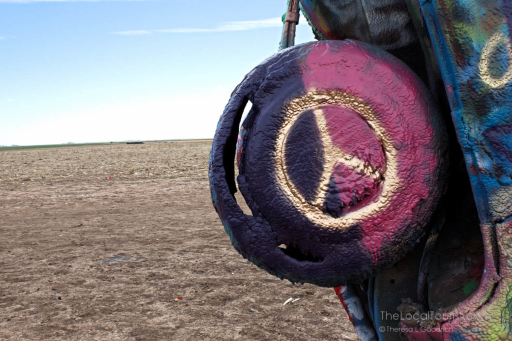Peace symbol painted in gold on tire of buried Cadillac