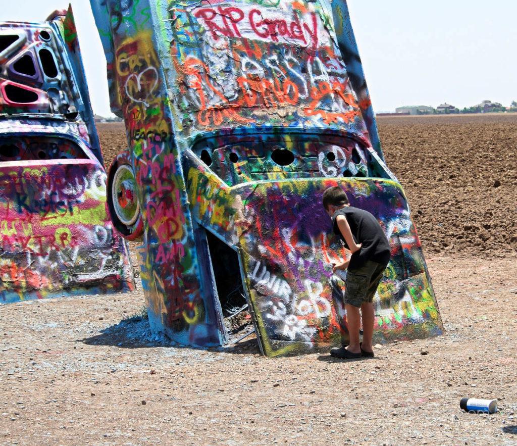 Boy spray painting at Cadillac Ranch