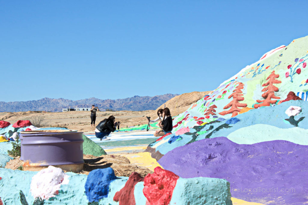 Young women taking photos at Salvation Mountain