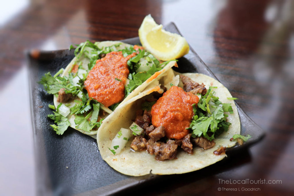 street-style carne asada tacos topped with house made salsa