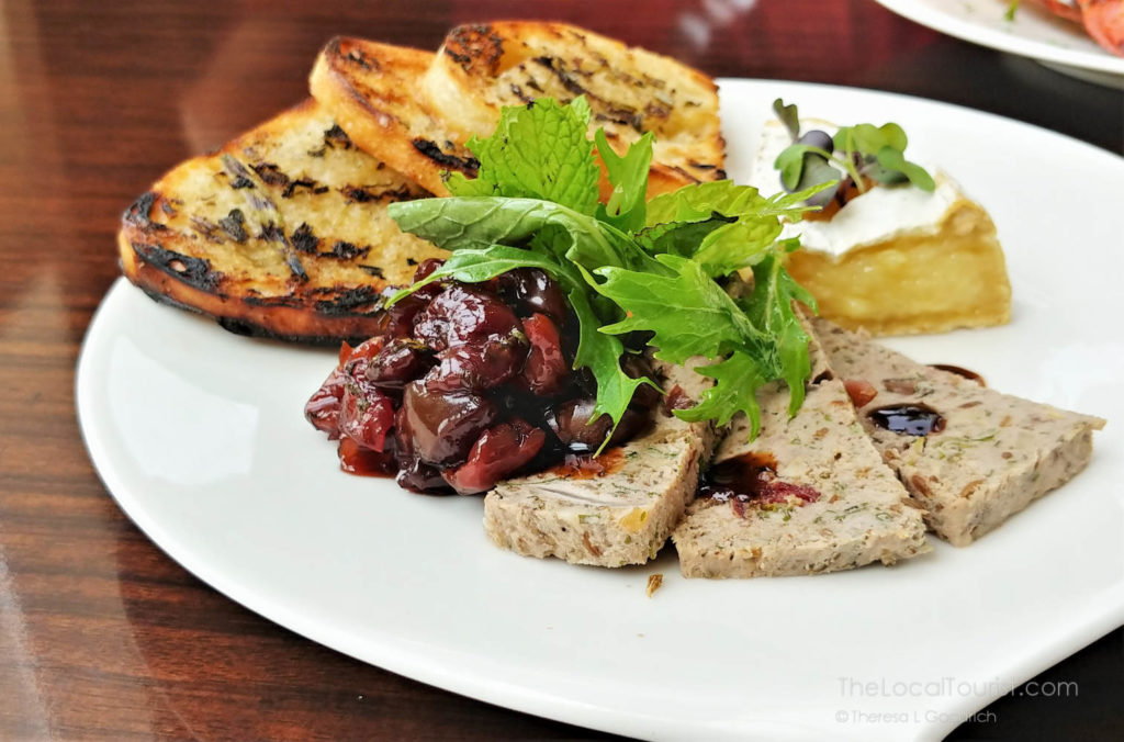 country pate with a cherry compote port sauce, warm camembert, crostini with rosemary butter, garnished with microgreens and a cucumber relish